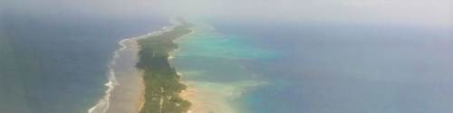 The picture shows the Marshall Islands from above - a long, small strip of land in a blue sea.
