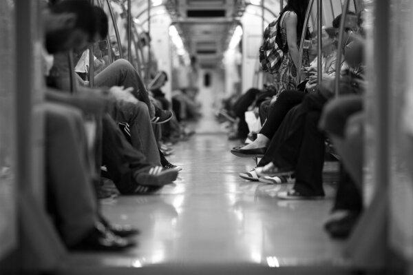 Schwarz-weiß Fotografie des Innenraums einer U-Bahn. Die Fotografie zeigt mittig, aus der Untersicht in Fahrtrichtung aufgenommen, verschiedene Personen, die rechts und links auf den Sitzen der Bahn Platz genommen haben. Der Kamerafokus liegt auf dem vorderen Bildmittelgrund und zeigt einige Schuhpaare in Schärfe. Die Gesichter und der Hintergrund wie auch der Vordergrund sind aufgrund der starken Unschärfe nicht zu erkennen.