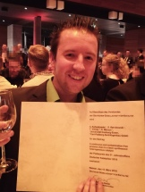 Picture of Sebastian Kohsakowski showing him smiling and holding up a glass of wine next to his price he won for the best poster in the german catalyst meeting in weimar.